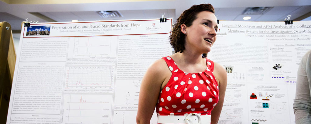 A student presents her research at a poster session.